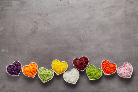 Liefde voor gezond voedsel concept met kleine hartvormige witte kommen geraspte groenten van verschillende kleuren op een rij op grijze oppervlakte achtergrond met kopie ruimte