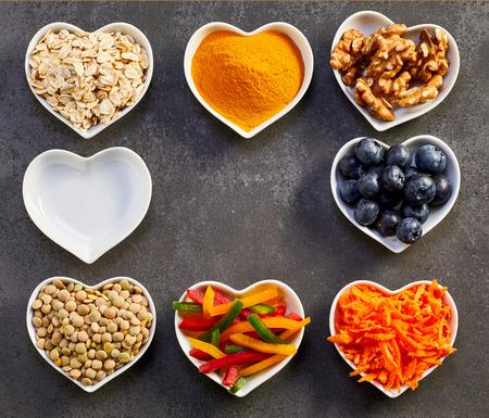 Reeks gezonde kokende ingrediënten in witte hart-vormige kommenstudio die van hierboven over grijze achtergrond met exemplaarruimte is ontsproten Stockfoto