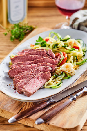 Delicious low carbohydrate meal with lean tender sliced roast beef served with a fresh vegetable salad with rustic utensils on a wooden chopping board