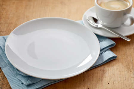 Empty white plate on blue napkin and cup of coffee with spoon on a saucer close-up on wooden table surface