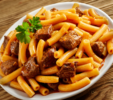 ridged: Plate of cubed grilled beef with Italian rigatoni pasta in a rich spicy sauce served on a white dish garnished with fresh parsley