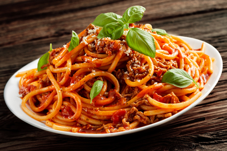 potherb: Heaped plate of traditional Italian spaghetti Bolognaise or Bolognese with a rich spiccy beef and tomato sauce topped with grated parmesan bd fresh basil leaves in a close up view on rustic wood Stock Photo