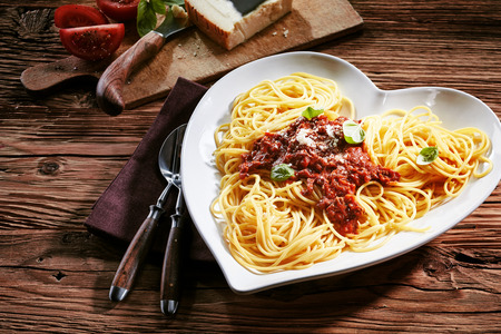 Plate of delicious spaghetti Bolognaise topped with grated parmesan cheese and fresh basil with the ingredients visible behind on a rustic textured wood table Фото со стока