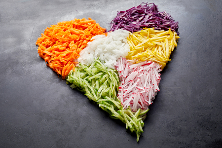 Heart-shaped pile of grated vegetables as ingredients for cooking placed over black surface background. Healthy organic food concept, close-up studio shot from above Stock Photo