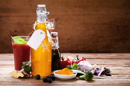 Healthy food ingredients rustic concept. Bottle with blank tag and vegetables still life on rough wooden table shot from the side with copy space background