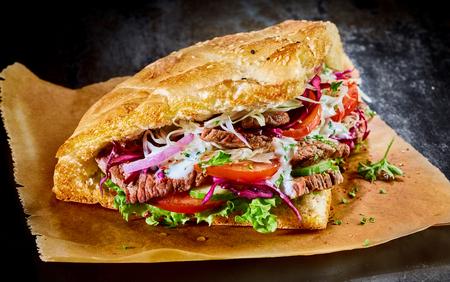 Doner kebab turco en pan tostado de oro pita lleno de carne asada de rotisserie y ingredientes de ensalada fresca servido en papel marrón