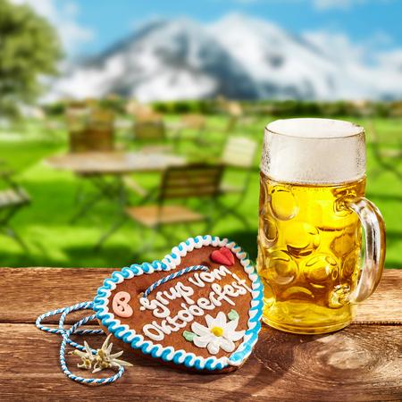 Oktoberfest-concept met een gemberhart met decoratieve suikerglazuur en een glaskroes van bier of lagerbier in openlucht op een rustieke herberglijst in Beieren met sneeuwbergen
