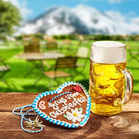 Oktoberfest concept with a ginger heart with decorative icing and a glass tankard of beer or lager outdoors on a rustic tavern table in Bavaria with snowy mountains Reklamní fotografie