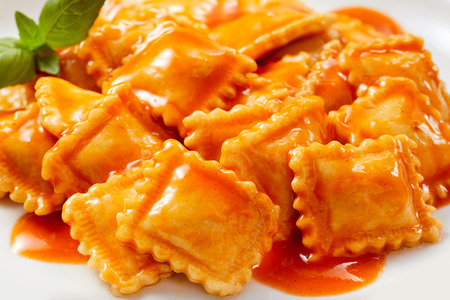 Homemade Italian ravioli pasta stuffed with savory meat served topped in spicy tomato sauce in a close up view cropped on a plate