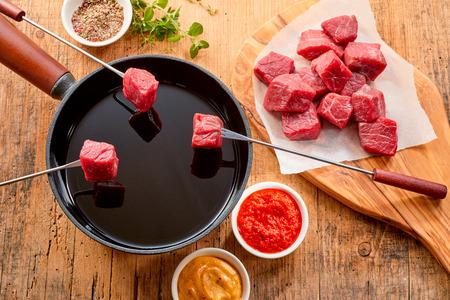 Mager prime beef gekookt in een fondue met in blokjes gesneden porties weergegeven op vorken boven de hete olie in de pot en kruiden, spice en dips weergegeven aan de zijkant, bovenaanzicht