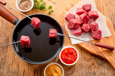 Tender prime beef being cooked in a fondue with cubed portions displayed on forks above the hot oil in the pot and herbs, spice and dips displayed to the side, overhead view