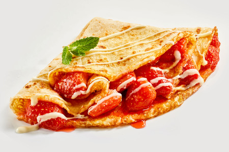 Fresh ripe red juicy strawberries in a golden fried crepe or French pancake drizzled with cream and garnished with mint over a white background Фото со стока