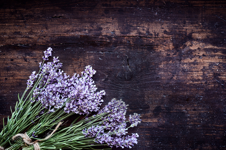 perfumery concept: Corner arrangement of lavender on rustic wood tied in bunches with string in a concept of spa treatments, alternate medicine or perfumery with copy space