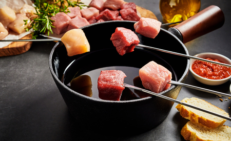 Assorted fresh lean meat ready for dipping in a fondue pot displayed on forks above the oil with ingredients, bread and dips to the sides