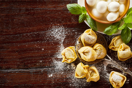 Freshly prepared uncooked handmade Italian tortellini pasta with basil and raw mushrooms on a floured wooden table with copy space Archivio Fotografico