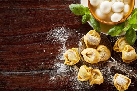 Vers voorbereide ongekookte met de hand gemaakte Italiaanse tortellinideegwaren met basilicum en de ruwe paddestoelen op a floured houten lijst met exemplaarruimte
