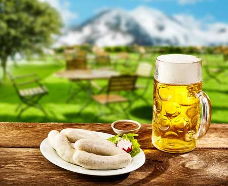 Traditional Oktoberfest cuisine with a plates of weissworst or veal sausages with a savory dip on a rustic tavern table with a glass of lager in the Bavarian Alps Stock Photo
