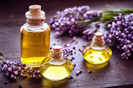 Bottles of lavender essential oil or extract with sprigs of fresh purple flowers on a rustic wood table in a healthcare or spa concept Banque d'images