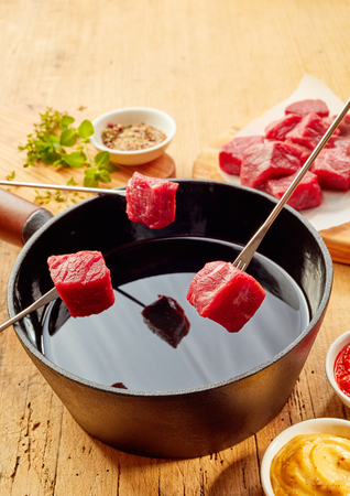 Prime tender beef being cooked in a fondue with diced portions displayed on forks over the hot oil in a pot on rustic wood with copy space