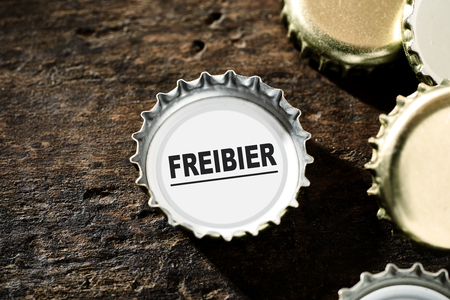 bier festival: free beer concept with gold metallic bottle tops on a rustic vintage wood background with one containing the text alongside copy space