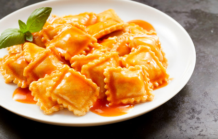 Plate of tasty traditional Italian ravioli pasta served in a piquant spicy sauce garnished with basil in a close up view