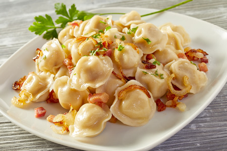 Serving of Russian regional pelmeni dumplings with a savory spicy meat stuffing in a close up view on the plate on a wood background