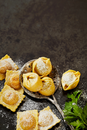 Fresh uncooked handmade Italian tortellini and ravioli pasta with a vintage spoon and basil on a dark textured surface with copy space viewed from above Stockfoto