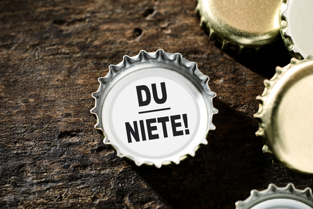 holz: Loosers concept with gold metallic bottle tops on a rustic vintage wood background with one containing the text alongside copy space