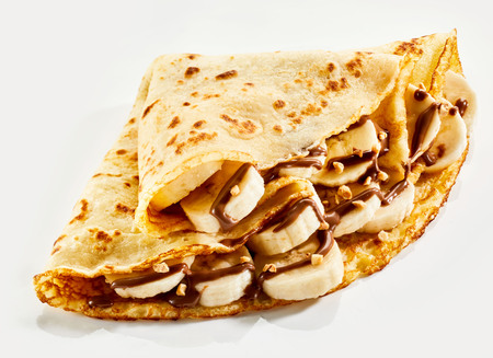 Fresh banana crepes drizzled with chocolate sauce and chopped nuts and folded into quarters on a white background Фото со стока