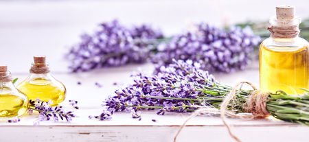Panorama banner of fresh lavender flowers tied in bunches and essential oils in decorative flacons on a white wood background with copy space and shallow dof for advertising