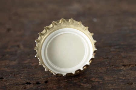Single gold metallic bottle cap from an alcoholic beverage or soft drink lying upside down on textured wood displaying the plastic inner coating