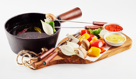 Colorful healthy vegetable fondue for vegetarians with diced bite size fresh raw sweet pepper, onion, mushrooms and broccoli served with dipping sauces