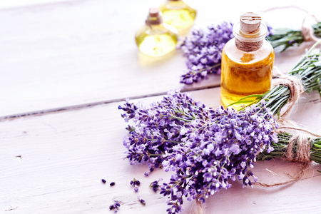 Spa background with bunches of fresh lavender flowers and bottles of natural extracts or essential oil on a toned lilac colored wood background with copy space 스톡 콘텐츠