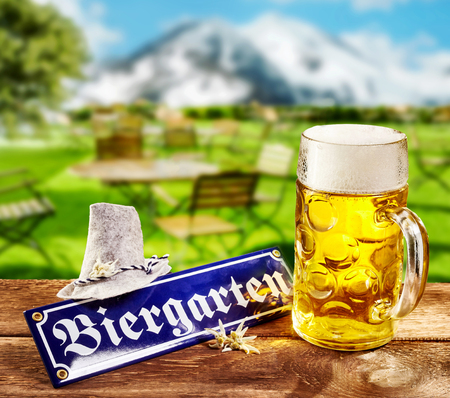 Biergarten or Beer Garden sign for Oktoberfest lying on a rustic outdoors wooden table at a tavern with a full frothy glass mug of beer and hat with a background view of the Bavarian Alps 版權商用圖片