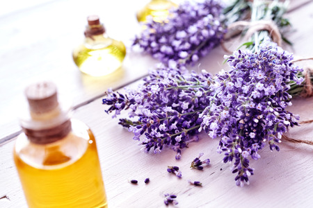 Fresh aromatic purple lavender flowers with bottles of essential oil or extracts in a spa, alternate medicine, perfumery and wellness concept on white wood