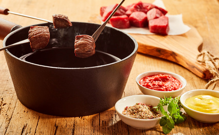 Spice rub, mustard and ketchup served with a meat fondue with portions of fried beef steak on forks suspended over a pot of hot oil Foto de archivo