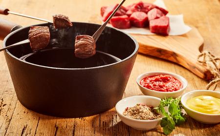 Gewürz reiben, Senf und Ketchup serviert mit einem Fleischfondue mit Portionen von gebratenem Rindersteak auf Gabeln über einem Topf mit heißem Öl