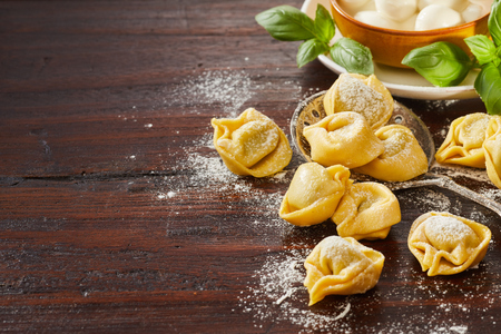 Freshly made uncooked Italian tortellini pasta with basil and mushrooms ready for cooling on a floured wooden table with copy space