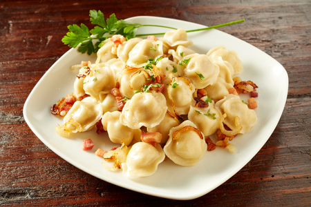 Serving of stuffed pelmini pasta dumplings a traditional Russian dish filled with spicy meat on a rustic wood table Stock Photo