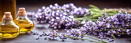 Panoramic banner or header of fresh purple lavender with flacons of essential oil for aromatherapy, alternate medicine and perfumery 스톡 콘텐츠