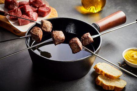 Cooking cubed portions of tender beef in a fondue pot with mustard and crusty French baguette to the side