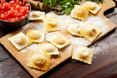 Speciality handmade uncooked Italian ravioli pasta with spicy salsa and parsley on a rustic wooden floured board in a close up view Zdjęcie Seryjne