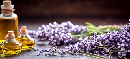 Panorama banner of decorative bottles of lavender essential oil with bunches of freshly picked aromatic purple flowers on a rustic wood table with copy space above