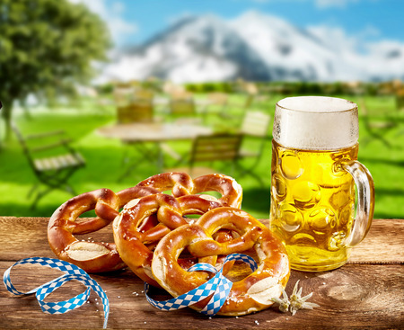 biergarten: Pretzels and frothy pint of beer in a glass tankard to celebrate Oktoberfest served on a rustic wooden table outdoors in a tavern with a view of the snowy alps Stock Photo