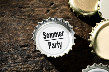 Summer Party or celebration concept with gold metallic bottle tops on a rustic vintage wood background with one containing the text alongside copy space