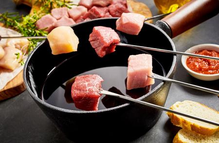 쇠고기, 송아지 고기, 돼지 고기, 닭 가슴살 퐁듀 냄비에 담근 준비가 된 모듬 된 고기