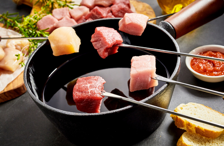 Assorted meat ready to be dipped in a fondue pot with beef, veal, pork and chicken breast displayed on forks
