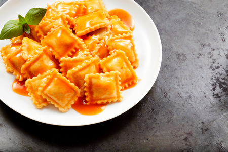 Fresh homemade Italian ravioli pasta served with a spicy tomato sauce and basil on a white plate over a textured grey background with copy space 版權商用圖片