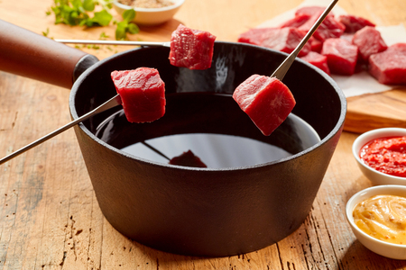 Lean tender beef steak displayed on forks over a fondue pot ready for dipping in the hot oil with mustard and tomato sauce to the side Stock Photo