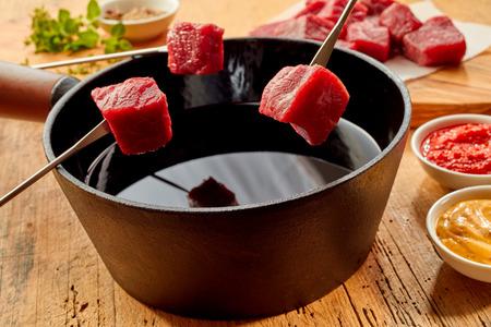 フォンデュ鍋の上にフォーク表示新鮮な立方体のステーキは調味料、マスタードとトマトのソース側と熱い油でいっぱい